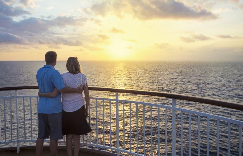 Paar op een cruise die op de zonsondergang letten over de oceaan stock foto's