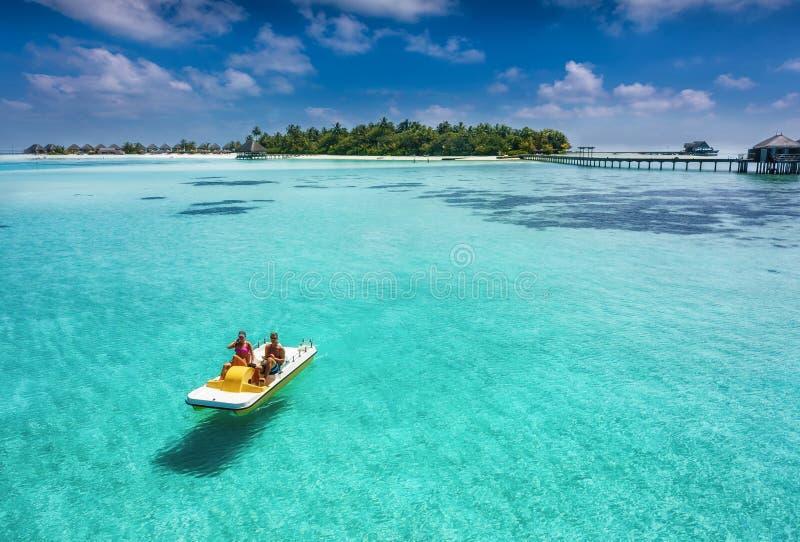 Paar op een drijvende pedaloboot op een tropische paradijsplaats royalty-vrije stock afbeeldingen
