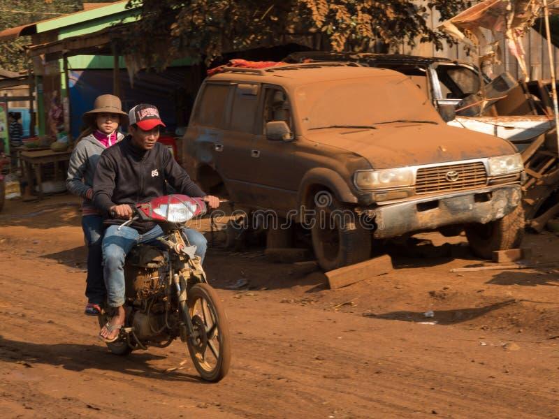Paar op een motor in een zeer stoffige straat stock afbeelding