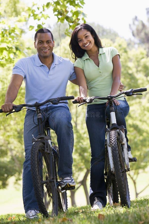 Paar op fietsen die in openlucht glimlachen royalty-vrije stock foto
