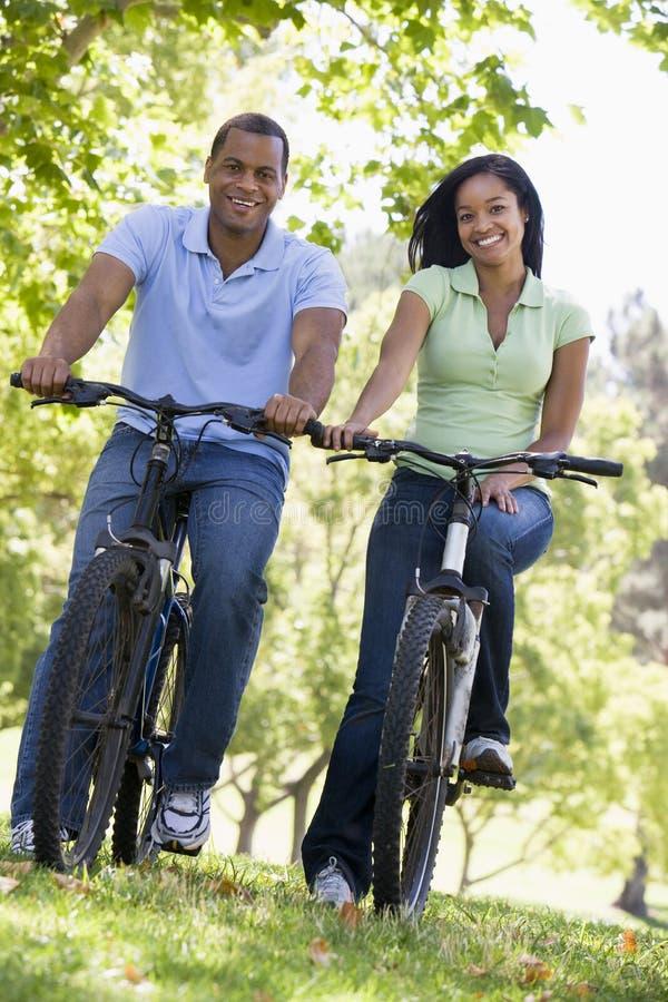 Paar op fietsen die in openlucht glimlachen royalty-vrije stock foto's