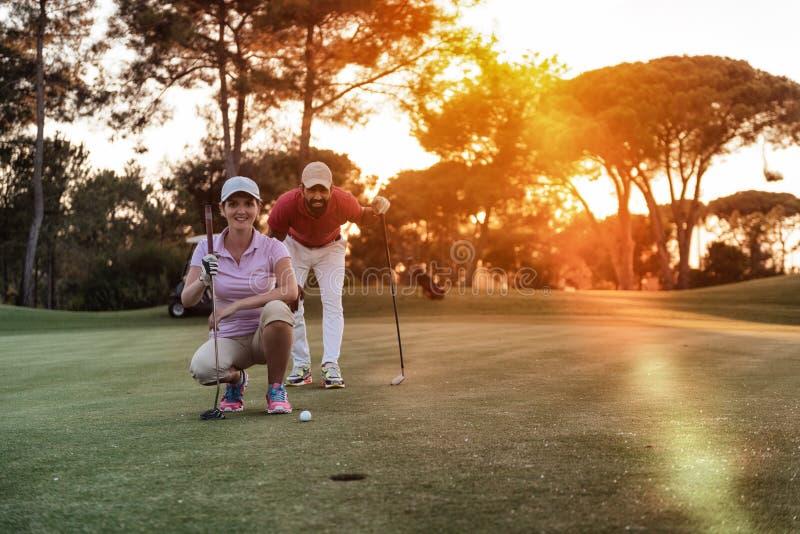 Paar op golfcursus bij zonsondergang stock foto