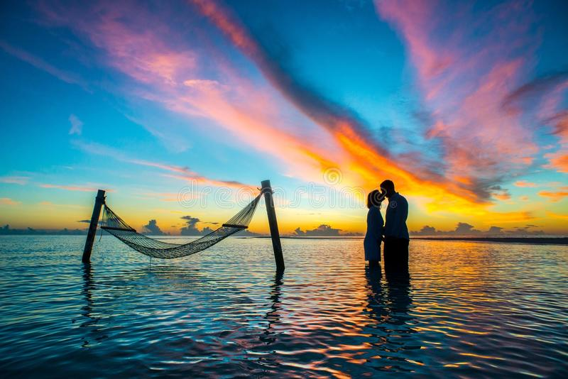 Paar op hangmat op zonsondergang stock foto