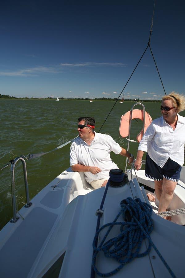 Paar op middelbare leeftijd bij boot het varen stock foto