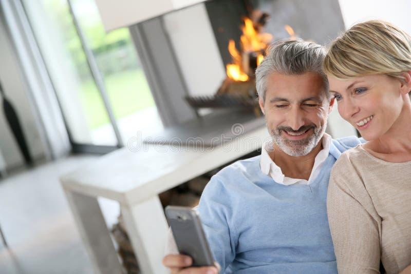 Paar op middelbare leeftijd door open haard thuis stock fotografie