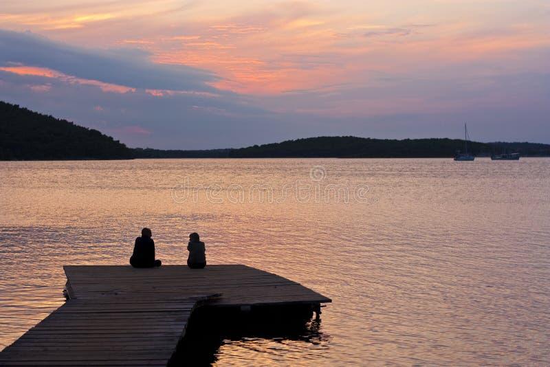 Paar op pijler met zonsondergang royalty-vrije stock foto's