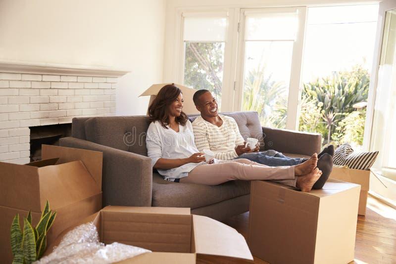 Paar op Sofa Taking een Onderbreking van het Uitpakken bij het Bewegen van Dag stock foto's