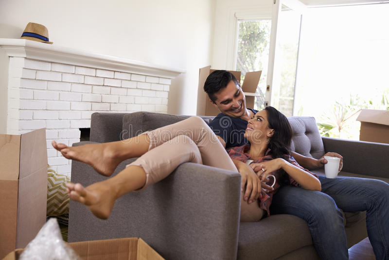 Paar op Sofa Taking een Onderbreking van het Uitpakken bij het Bewegen van Dag royalty-vrije stock afbeeldingen