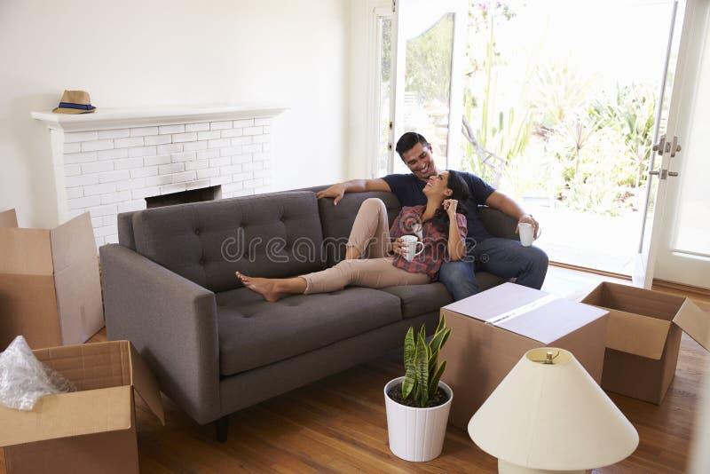 Paar op Sofa Taking een Onderbreking van het Uitpakken bij het Bewegen van Dag stock fotografie
