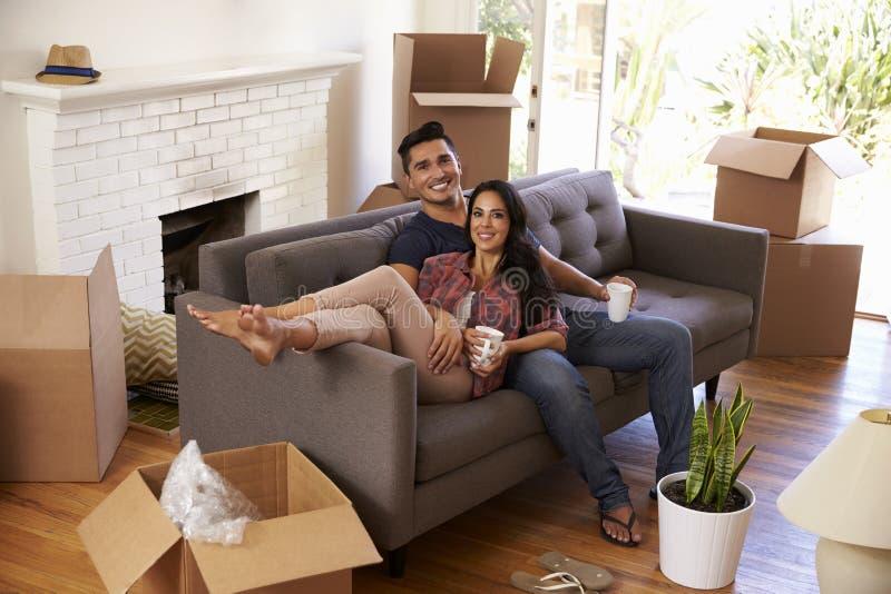 Paar op Sofa Taking een Onderbreking van het Uitpakken bij het Bewegen van Dag royalty-vrije stock foto