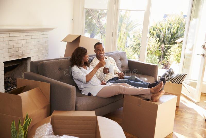 Paar op Sofa Taking een Onderbreking van het Uitpakken bij het Bewegen van Dag stock foto