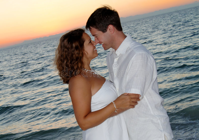 Paar op strand bij zonsondergang royalty-vrije stock afbeelding