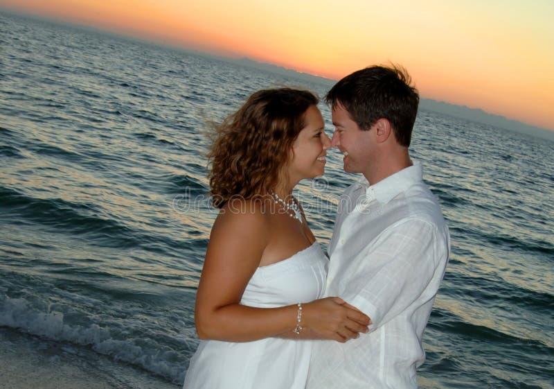 Paar op strand bij zonsondergang royalty-vrije stock foto's