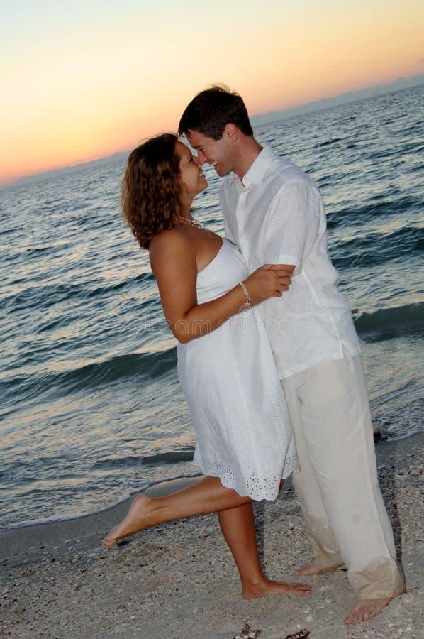 Paar op strand bij zonsondergang royalty-vrije stock afbeeldingen