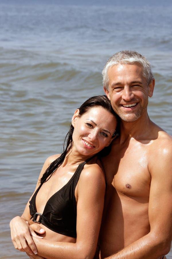 Paar op strand het koesteren stock fotografie