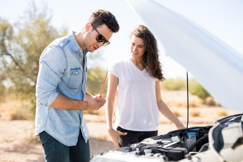 Paar op wegreis met opgesplitste auto stock afbeelding