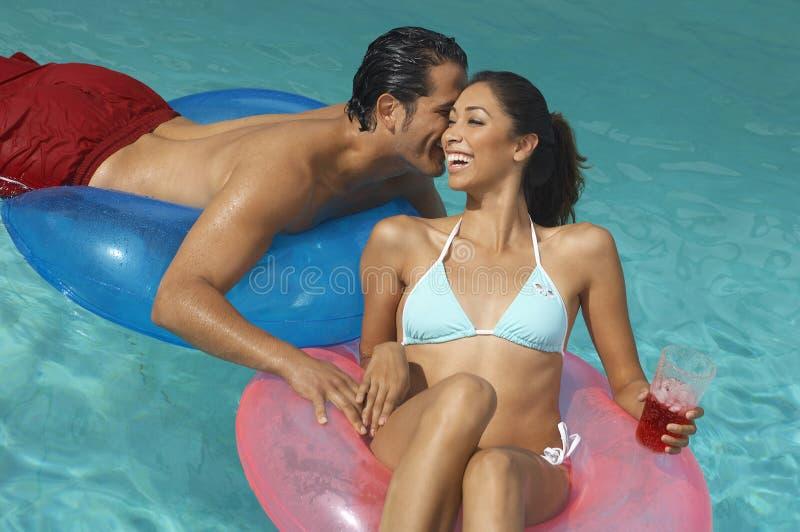Paar in Opblaasbare Ringen die bij Pool fluisteren stock foto