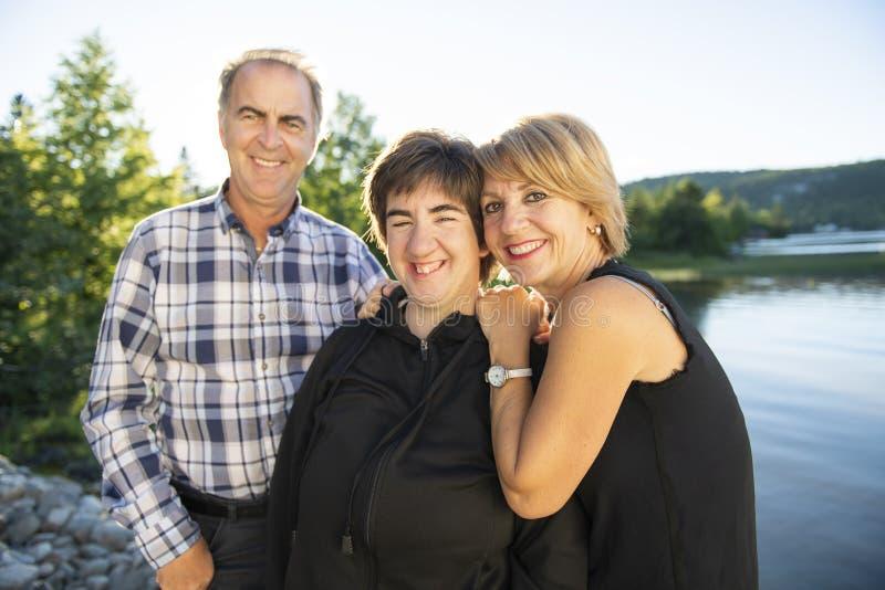 Paar in openlucht met gehandicapte persoonsdochter door meer die goede tijd hebben royalty-vrije stock afbeelding