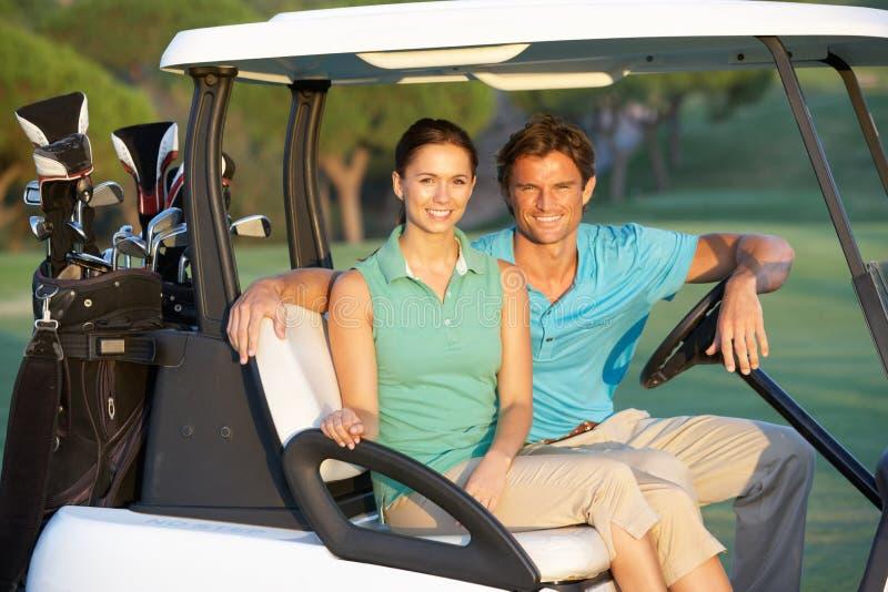 Paar-Reiten im Golf-Buggy stockfoto