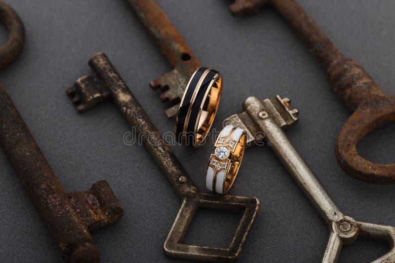 Paar ringen van het huwelijksemail op grijze achtergrond met uitstekende roestige sleutels royalty-vrije stock afbeelding