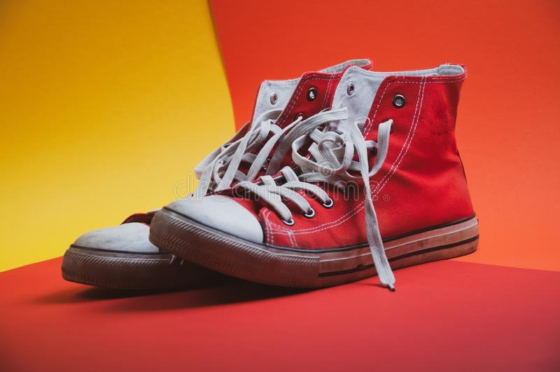 Paar rode gebruikte tennisschoenen op kleurrijke achtergrond, mening van kant stock fotografie