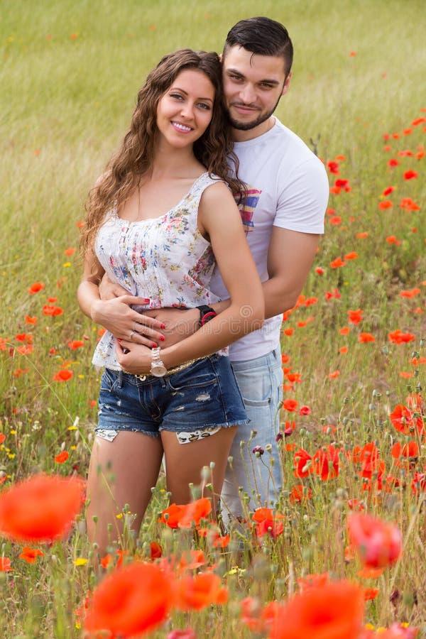 Paar in rode papavers royalty-vrije stock afbeelding