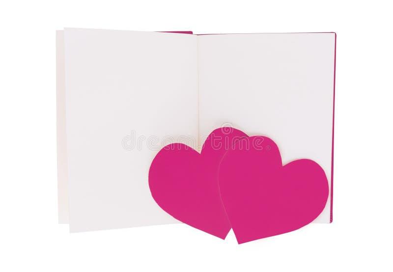 Paar roze document hart op leeg open die boek op wit wordt geïsoleerd royalty-vrije stock afbeeldingen