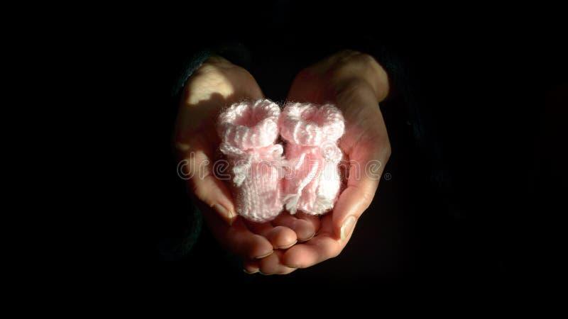 Paar Roze Gebreide Babybuiten in de Hart Gevormde Palmen van a stock afbeeldingen