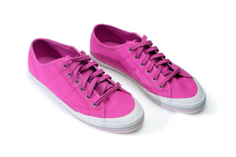 Paar roze gumshoes Fuchsiakleurig die tennisschoenen op een wit worden geïsoleerd stock foto's