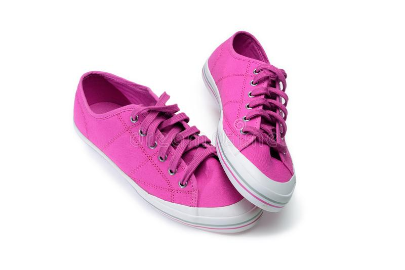 Paar roze gumshoes Fuchsiakleurig die tennisschoenen op een wit worden geïsoleerd stock fotografie