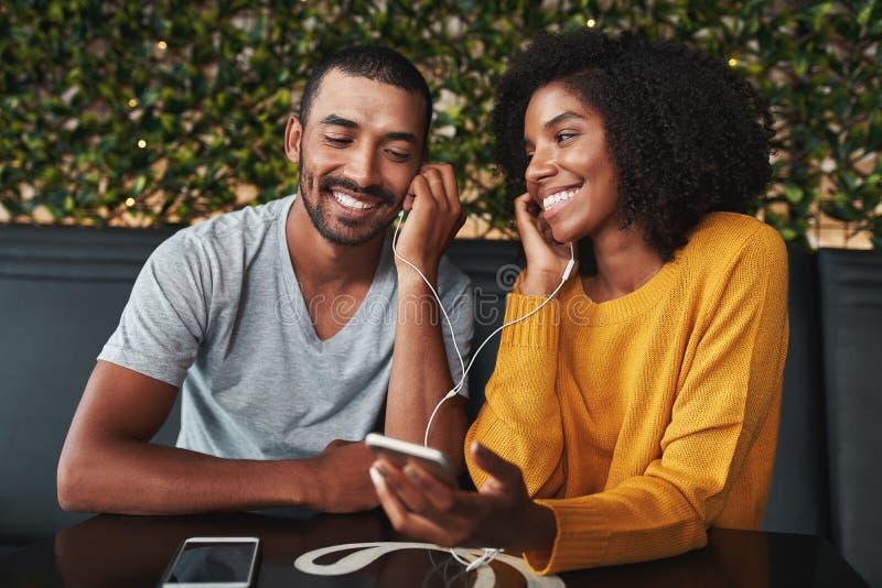 Paar samen het luisteren muziek in koffiebar stock fotografie