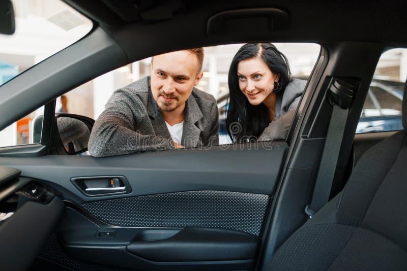 Paar schaut auf Innenraum des Neuwagens im Ausstellungsraum stockbild