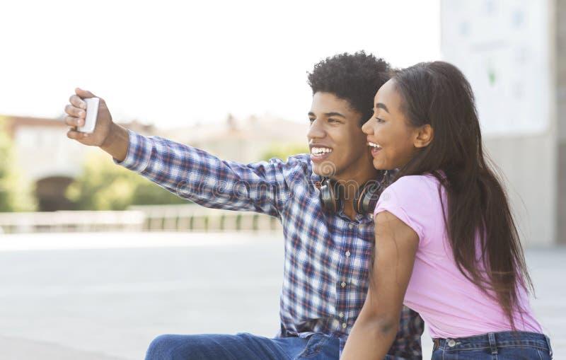 Paar Selfie Tienermeisje en jongen die fotograferen op smartphone stock afbeelding