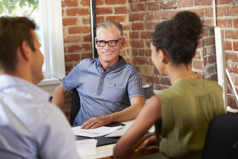 Paar-Sitzung mit Finanzberater im Büro lizenzfreie stockfotos