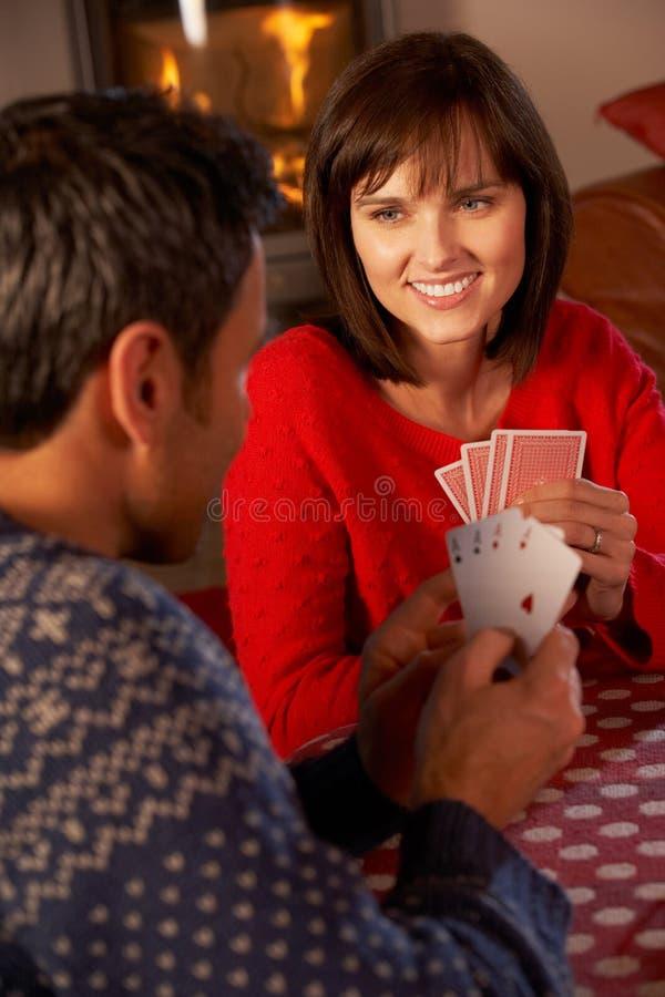 Paar-Spielkarten durch Cosy Protokoll-Feuer lizenzfreies stockfoto