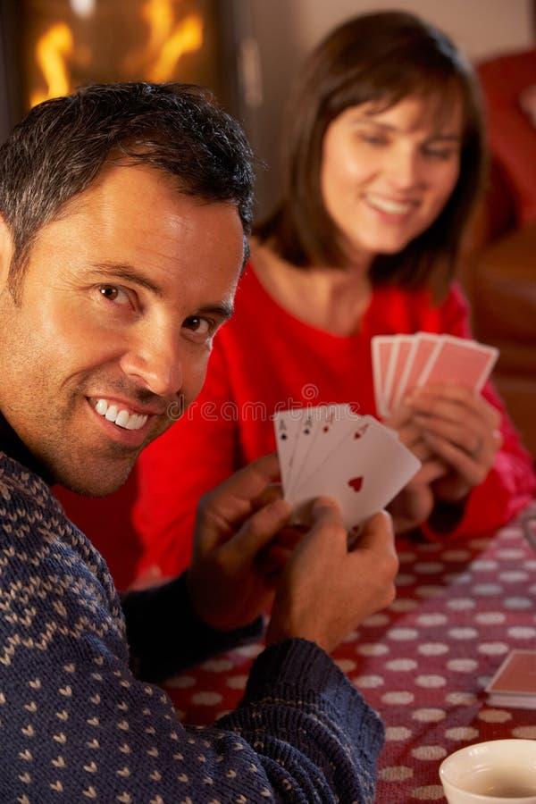 Paar-Spielkarten durch Cosy Protokoll-Feuer lizenzfreie stockfotos