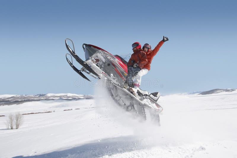 Paar-springendes Schneemobil fahrung im Schnee lizenzfreie stockbilder