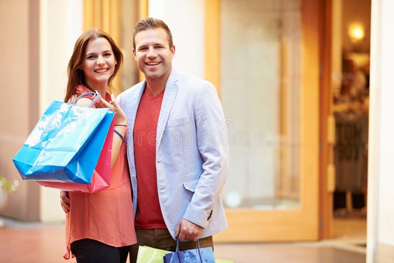 Paar-stehender Außenseiten-Speicher im Mall, das Einkaufstaschen hält lizenzfreies stockfoto