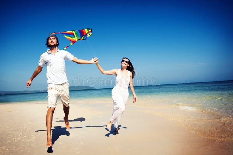Paar-Strand-Drachen-Fliegen-Flucht-Feiertags-Konzept lizenzfreie stockfotos