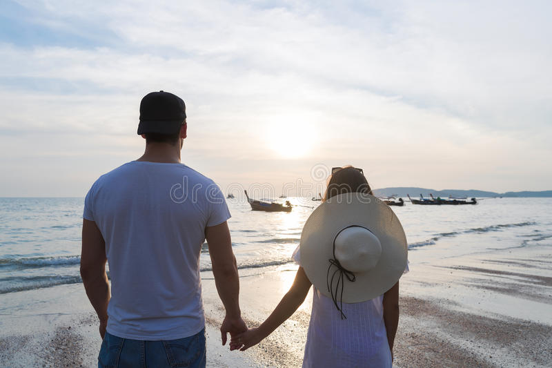 Paar-Strand-Sommer-Ferien, Mann-Frauen-Händchenhalten-Sonnenuntergang-Junge Guy Girl Back Rear View lizenzfreies stockbild