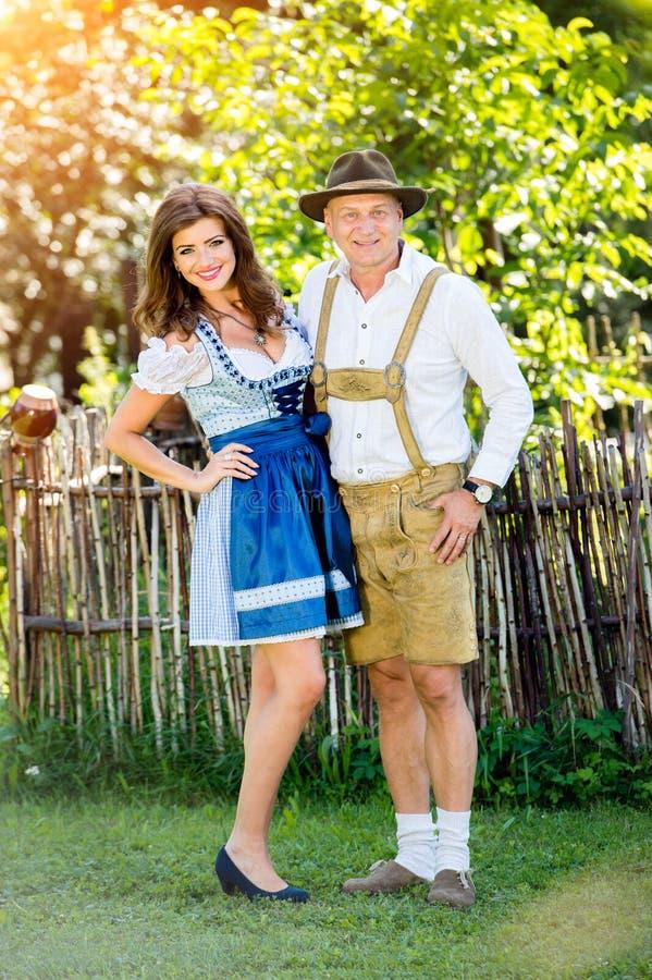Paar in traditionele Beierse kleren die zich in de tuin bevinden stock fotografie