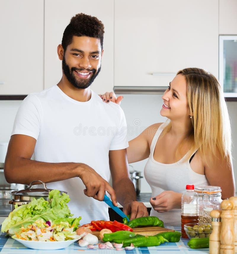 Paar tussen verschillende rassen kokende groenten stock fotografie