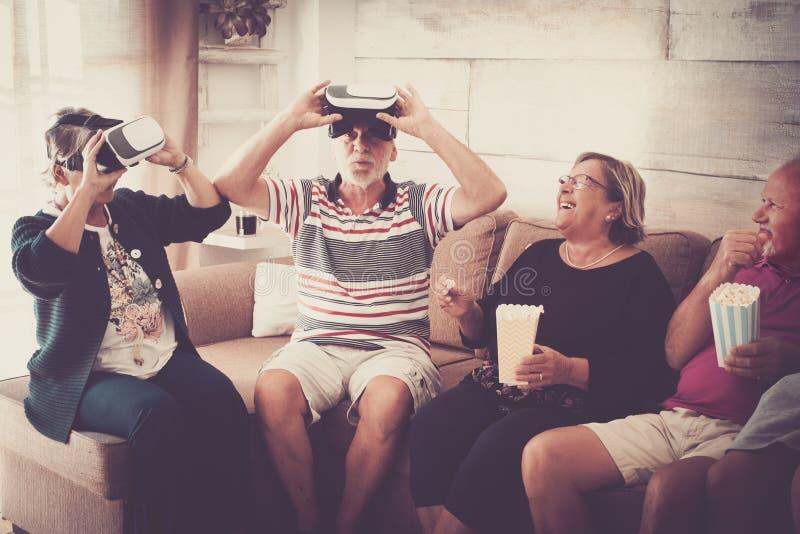 Paar twee van hogere volwassenen geniet thuis van de dag met pop graan en de virtuele hoofdtelefoon goggled oogglas nieuwe techno stock afbeeldingen