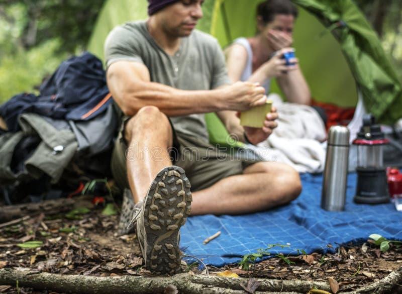 Paar uit voor het kamperen in bos stock afbeeldingen