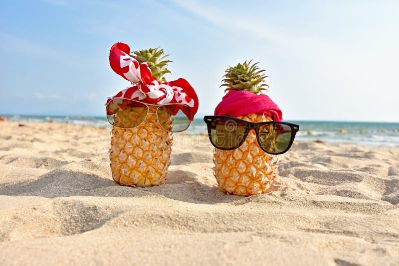 Paar van ananas met zonnebril op tropisch strand royalty-vrije stock afbeelding