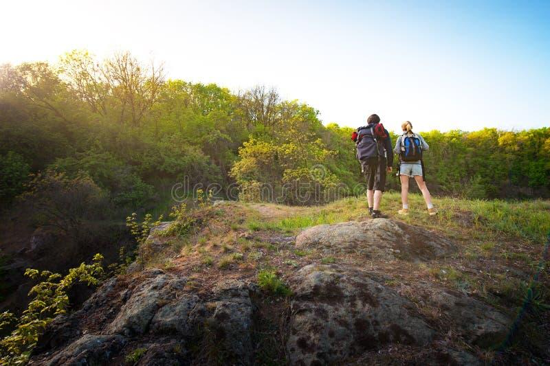 Paar van backpackers of wandelaarstribunes op bergbovenkant bij zonsondergang stock foto's