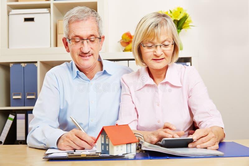 Paar van bejaarden die voor hypotheek het lenen plannen stock afbeeldingen