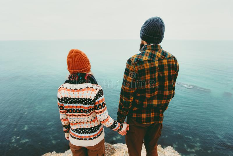Paar in van de liefdeman en Vrouw holdingshanden samen boven overzees op concept van de de emotieslevensstijl van de klippenreis  stock foto
