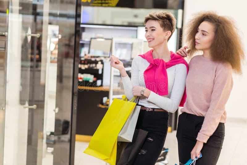 Paar van diverse vrouwen die smth in winkelshowcase bekijken in het warenhuis royalty-vrije stock afbeeldingen