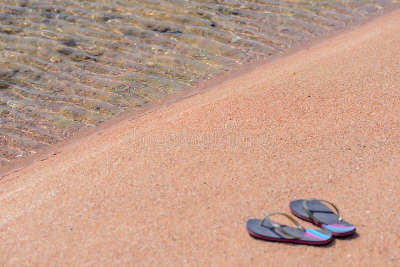 Paar van Flip Flops bij Oever van Sandy Beach stock fotografie